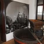 Szőlődaráló, mögötte  a szüreti munka képe / Schrotmühle, dahinter ein Bild von der Ernte